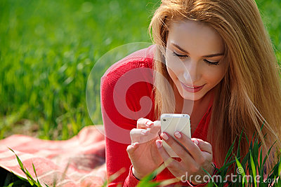 Close up of woman using mobile smart phone in the Park.