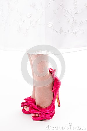 Close up of womans feet in hot pink stilettos