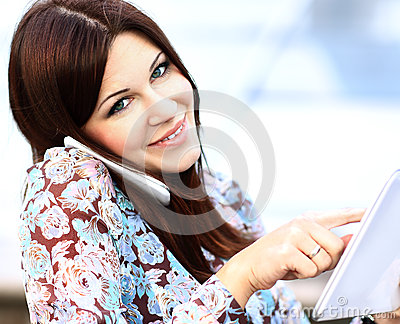 Close up of young businesswoman using digital tablet and mobile phone