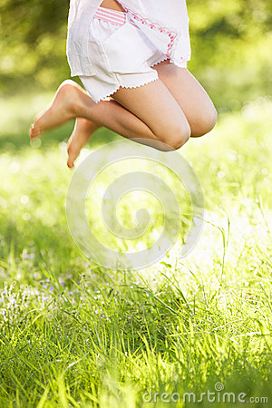 Close Up Of Young Girl Jumping In Summer Field