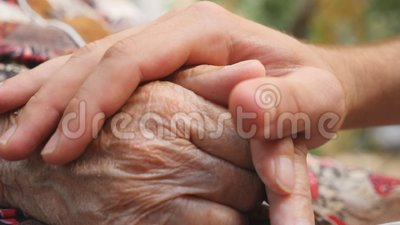 Close up of young male hand comforting an elderly arms of old woman outdoor. Grandson and grandmother spending time. Together outside. Concept of care and love stock video