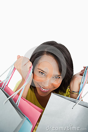 Close-up of a young woman showing shopping bags