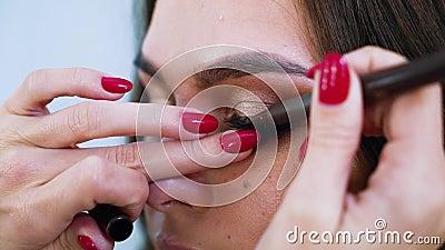 Close-upmening die van vrouwelijke handen eyeliner op de oogleden van de jonge aantrekkelijke vrouw toepassen stock videobeelden