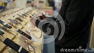 Close-upmening van jonge mensen` s handen die een nieuwe mobiele telefoon in een winkel kiezen Hij probeert hoe het werkt stock video