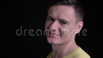 Close-upportret in profiel van de Kaukasische mens op middelbare leeftijd in het gele sweater letten smilingly op in camera op zw stock videobeelden