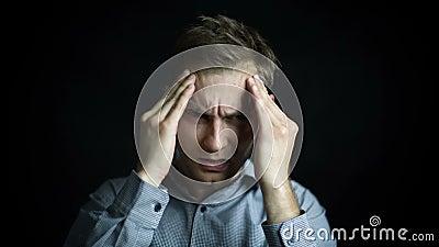 Close-upportret van de beklemtoonde die mens met hoofdpijn, op zwarte achtergrond wordt geïsoleerd stock video