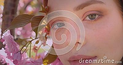 Close-upportret van het mooie gember model letten op vreedzaam en prettily in camera op roze bloemenparkachtergrond stock videobeelden