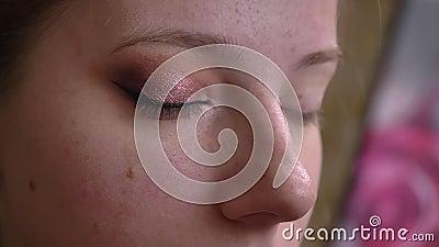 Close-upportret van jonge Kaukasische vrouwelijke make-upkunstenaar die de zwarte eyeliner aanvragen mooie pijlen stock video