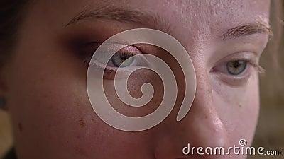 Close-upportret van jonge Kaukasische vrouwelijke make-upkunstenaar die witte eyeliner toepassen op haar lager ooglid stock footage