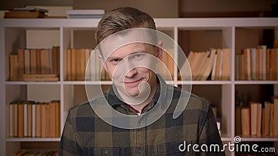 Close-upspruit van het jonge aantrekkelijke Kaukasische mannelijke student glimlachen met opwinding die camera in de universiteit stock video