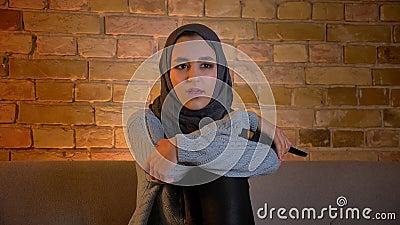 Close-upspruit van jong aantrekkelijk moslimwijfje in hijab die op TV met opwinding letten en afstandsbediening houden terwijl stock footage