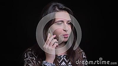 Close-upspruit van jong attractiver Kaukasisch wijfje die een toevallig gesprek op de telefoon voor de camera hebben stock footage