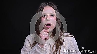 Close-upspruit van jong vrij donkerbruin Kaukasisch wijfje die met een roddel worden geschokt en wordt verrast stock footage