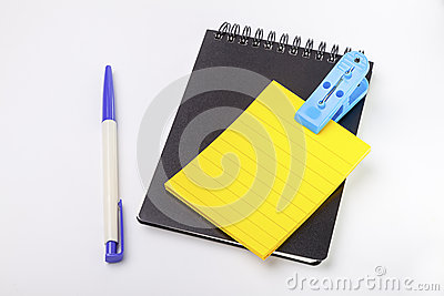 Closed black cover notebook ,yellow empty post note and pen