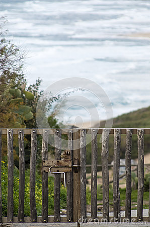 Closed gate of rough logs and behind the sea