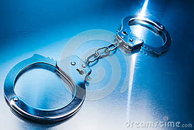 Closed handcuffs on a metallic background with dramatic lighting
