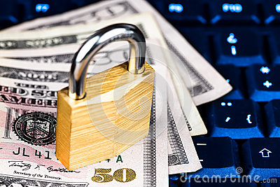 Closed padlock over a stack of money on a keyboard