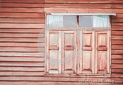 Closed vintage wooden window on wooden wall