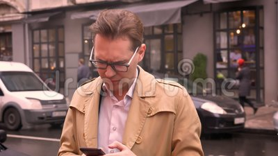 Closeup of adult caucasian man awaiting for someone standing on the street checking phone nervously.  stock video