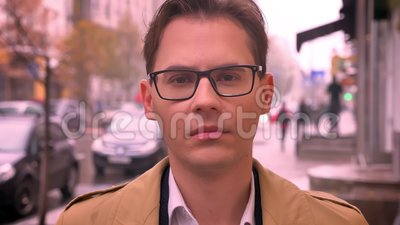 Closeup of adult caucasian man faced to camera looking forward in glasses standing on the street by the road and passing. Cars stock video footage