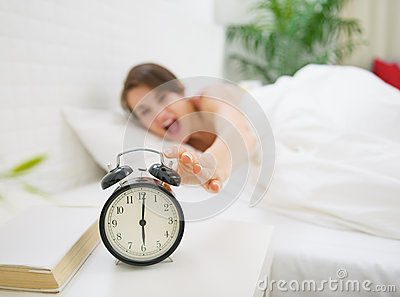 Closeup on alarm clock and angry woman in background