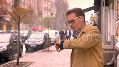 Closeup of attractive caucasian man awaiting looking around and at the watch. Leaving after he sees the person.  stock video footage