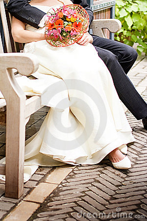 Closeup of bride and groom sitting in a park