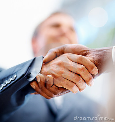 Closeup: Business men shaking hands over a deal
