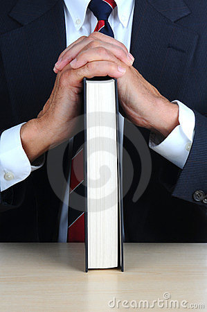 Closeup of a businessman leaning on book at desk