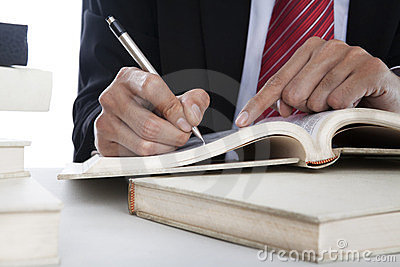 Closeup of businessman writing on a book