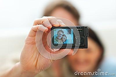 Closeup on camera making portrait of couple