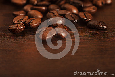 Closeup of coffee beans on a dark wooden surface