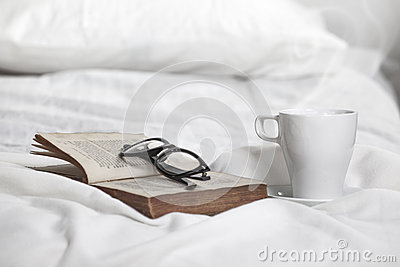 Closeup of a cup of coffe, old book and rimmed glasses on a white pillow.