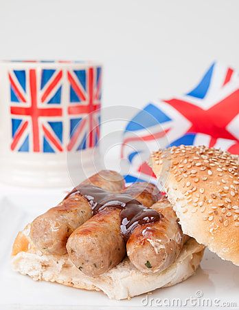 Closeup of English sausage sandwich with, brown sauce, cup of te