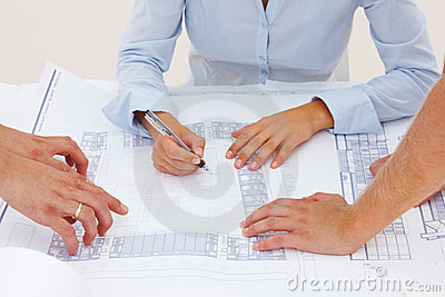 Closeup of female architect's hands on blueprints