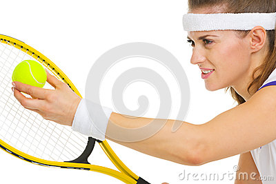 Closeup on female tennis player serving ball