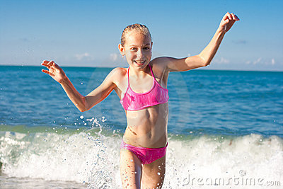 Closeup girl running from sea wave