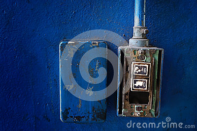 Closeup grunge light switch on blue wall