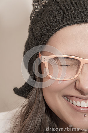 Closeup half face portrait of funny laughing woman with winter hat and summer glasses
