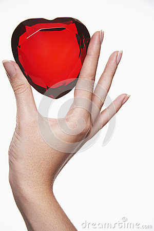 Closeup Of Hand Holding Up Heart Shaped Jewel