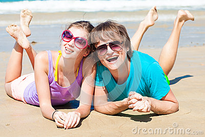 Closeup of happy young couple in sunglasses lying