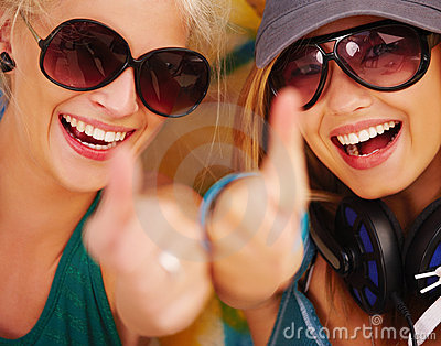Closeup of happy young girls showing thumb s up si