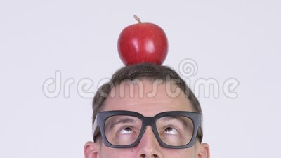 Closeup head shot of nerd man with apple on head. Studio shot of nerd man wearing eyeglasses against chroma key with white background stock footage