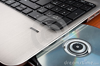 Closeup image of a laptop and CD