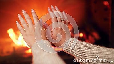 Closeup 4k vidéo d'une jeune femme frottant les mains et réchauffant le doigt froid près du feu dans la cheminée à la maison banque de vidéos