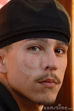 A closeup of a latino gang member looking fearsome