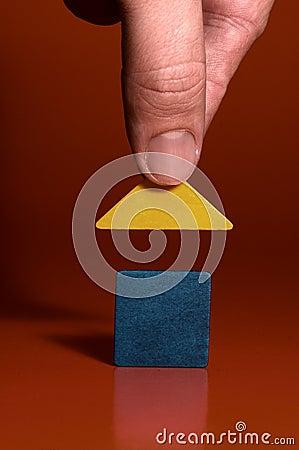 Closeup of a mans hand building a house