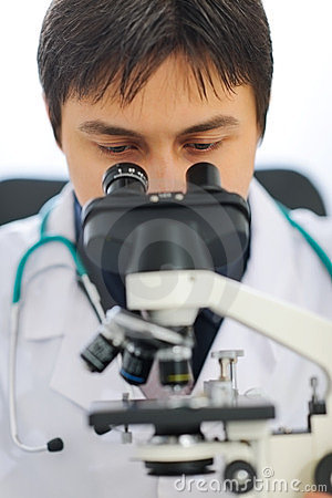 Closeup on medical doctor looking in microscope