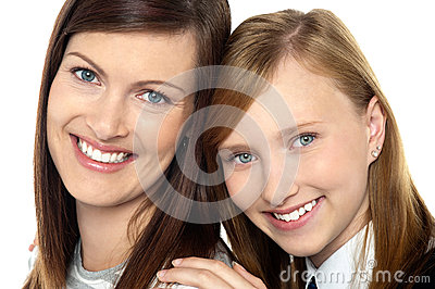 Closeup of mom and daughter flashing a smile