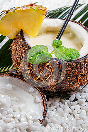 Closeup of pinacolada in coconut on beach